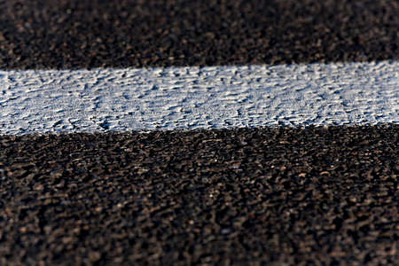 carriageway: photographed close-up of the new road for the movement of vehicles, a dark cover the carriageway road markings - white stripes