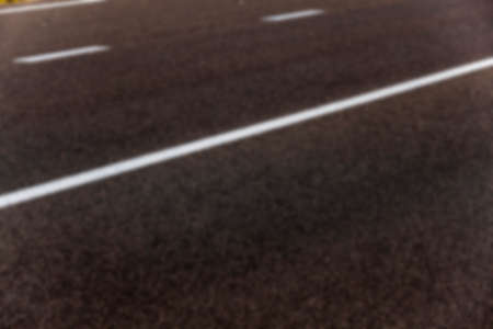 carriageway: photographed close-up of the new road for the movement of vehicles, a dark cover the carriageway road markings - white stripes, defocus