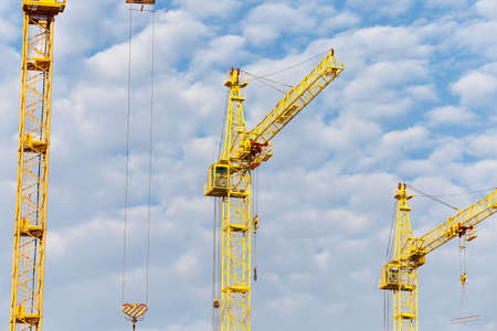 public housing: photographed close-up construction cranes during construction of a new multi-storey apartment building, blue sky and clouds, Stock Photo