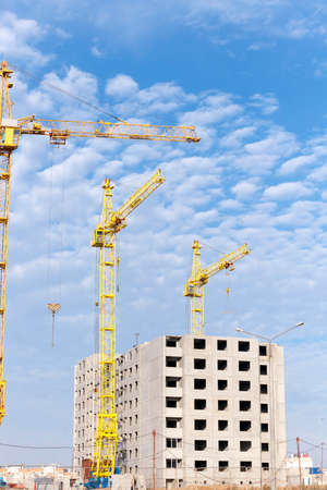 working stiff: photographed close-up construction cranes during construction of a new multi-storey apartment building, blue sky and clouds, Stock Photo