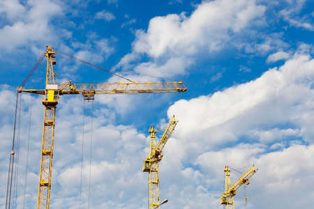 photographed close-up construction cranes during construction of a new multi-storey apartment building, blue sky and clouds, Stock Photo