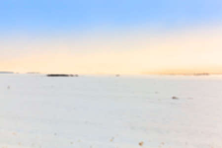 defocus: farm field photographed in winter, covered with white snow, sunset in the background defocus