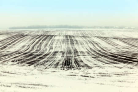 defocus: farm field photographed in winter, covered with white snow, blue sky in the background defocus Stock Photo