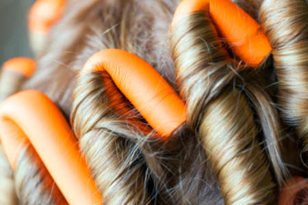 photographed close-up of orange curlers, hair twisted into a dark, defocus Stock Photo