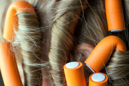 photographed close-up of orange curlers, hair twisted into a dark, Stock Photo