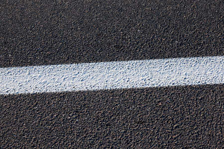 double lane: photographed close-up of the new road for the movement of vehicles, a dark cover the carriageway, Stock Photo