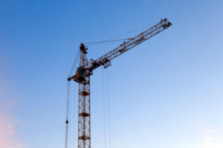 working stiff: photographed close-up construction cranes during construction of a new multi-storey residential building, defocus