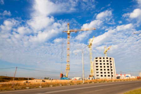 photographed close-up construction cranes during construction of a new multi-storey apartment building, blue sky and clouds, defocus Stock Photo