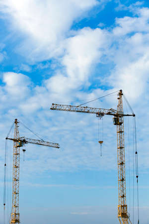 storey: photographed close-up construction cranes during construction of a new multi-storey apartment building, blue sky and clouds, Stock Photo