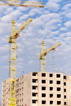 constructional: photographed close-up construction cranes during construction of a new multi-storey apartment building, blue sky and clouds, Stock Photo