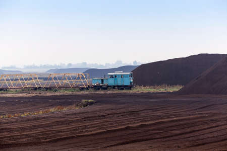 peaty: bog and the field on which the production is carried out in black peat mining, industry, old blue train