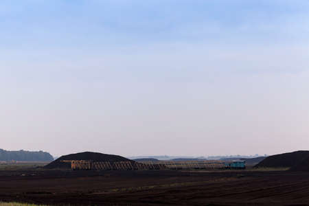 bog and the field on which the production is carried out in black peat mining, industry, old blue train