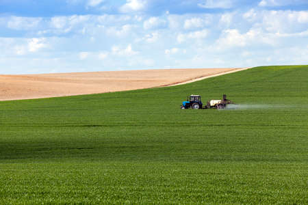 palate: tractor, photographed in the agricultural field during handling pesticides. sky with clouds Stock Photo