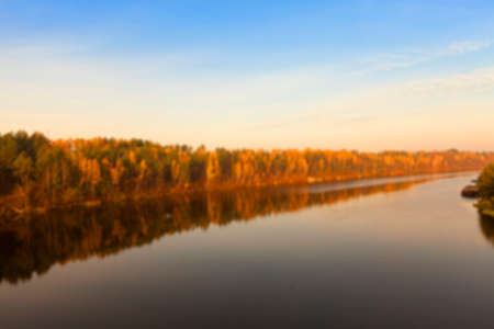 yellowing: the river photographed during the autumn season, the yellowing trees, sun time dawn, defocused Stock Photo