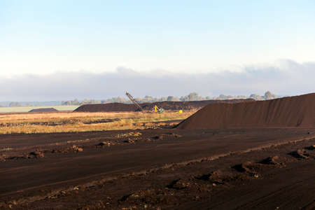 dragline: bog and the field on which the production is carried out in black peat mining, industry, old tractor