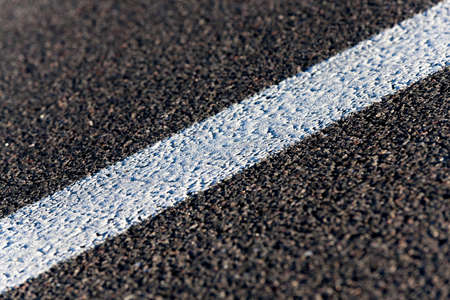 double lane: photographed close-up of the new road for the movement of vehicles, a dark cover the carriageway road markings - white stripes