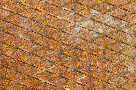 heavy industry: close-up photo of a metal plate with a protruding grid pattern covered in orange rust. Small depth of field.