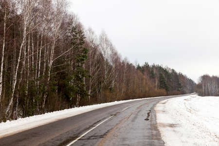 Traces left by car on the snow-covered road in the winter season. Photo closeup in cloudy weather. The road passes through the forest with trees