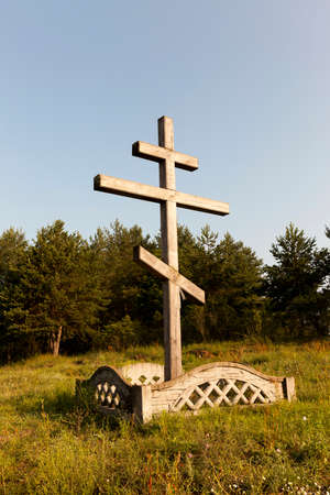 close-up photograph of a wooden religious Christian cross set near a forest. Blue sky in the background Stock Photo
