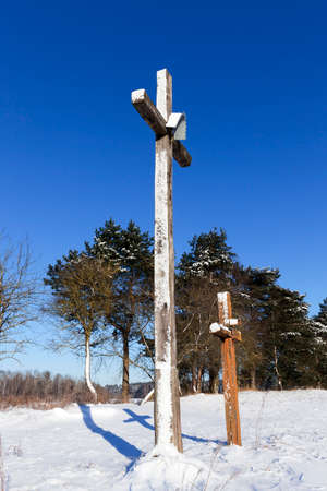 photographed close-up in the winter season of a wooden religious Christian cross set near the forest. Blue sky in the background Stock Photo