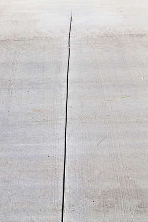 The texture of the road, built of gray concrete. photo close-up of the place of connection and docking of individual concrete slabs.