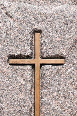 A wooden Catholic cross fixed on a stone. Religious symbols close-up photo Stock Photo