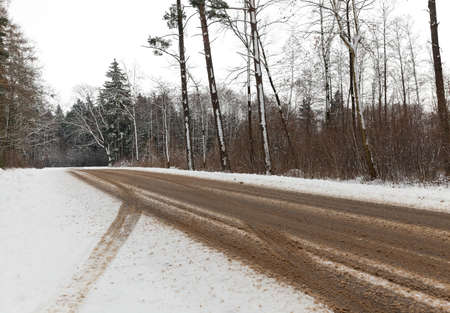 snowed: car paved road, where the snow melted. On the snow prints of the car wheels visible. On the side of the road is growing forest. Stock Photo