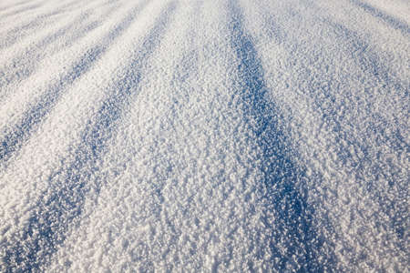 clean surface of snow in winter. photo close-up with discernible crystals of snow and ice. view at an angle, shallow depth of field.