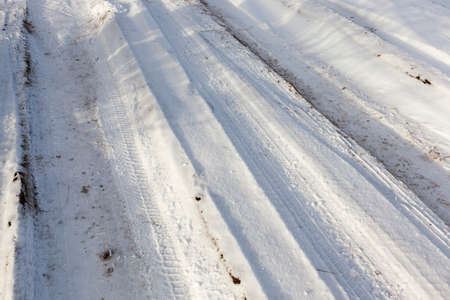 deep track on dirty snow on the road without asphalt. close-up, view at an angle. winter day in the forest Stock Photo