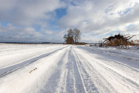 curve road: rural road covered with snow in the winter. There are traces of the car. Against the background of the blue sky.