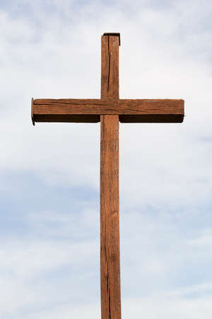 Old religious cross of wood against the blue sky. Photo close-up. Religious symbols of Christianity