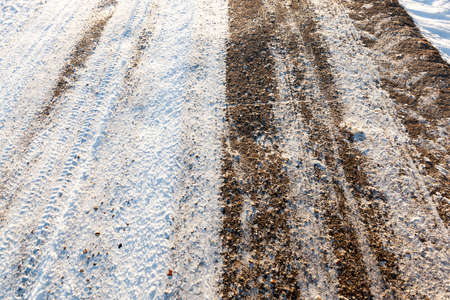 the snow-covered asphalt road in the winter season. Photographed close-up. Stock Photo