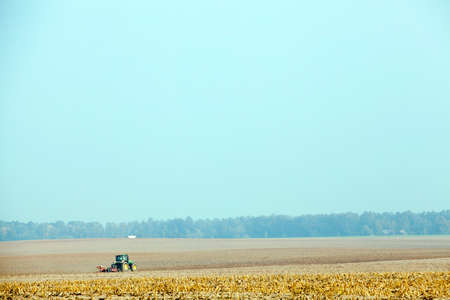 photographed close-up of a cloud on a blue sky. Small depth of field. On the field a tractor plows an agricultural field