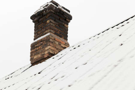 tall chimney: photograph of the roof of a house made of slate covered with snow falling during a snowfall