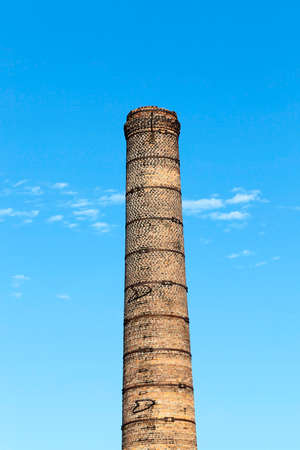 close-up photo of a pipe from a stove made of bricks. blue sky