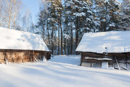 old wooden buildings in the forest in the winter season. On the surface of buildings and the ground lies snow