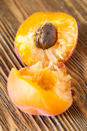 broken hands with ripe fruit of apricot, orange, photo close-up of flesh with bone on a wooden table