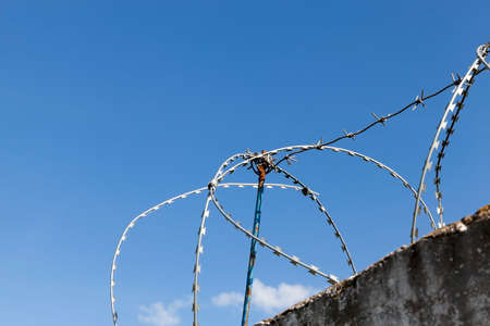 old dirty and high concrete fence on top of which is wound a new metal wire to protect the territory, against a background of blue sky close-up Stock Photo