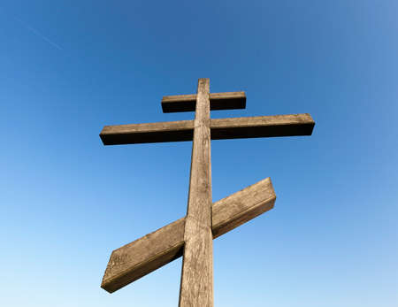 old wooden orthodox cross against the blue sky, closeup photo