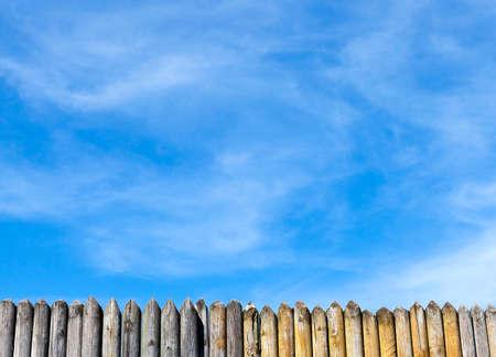 een klein deel van de scherpe palissade van dennenhout tegen de blauwe lucht, het landschap in de lente