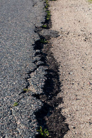 edge with cracks and other details of an asphalt road and roadside from sand, closeup photo Reklamní fotografie