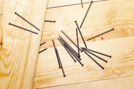 The metal nails lying on wooden boards until they are used and hammered into the boards, closeup