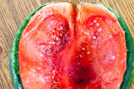 red juicy pulp of ripe watermelon of small size, covered with mold, dangerous food closeup