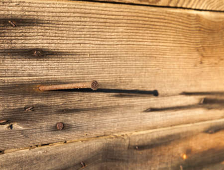 old metal nail with rust hammered into old wooden boards when building in a barn village, closeup Stok Fotoğraf