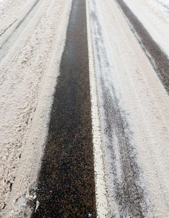 Traces of cars on the asphalt road in the winter season, close-up Stock Photo