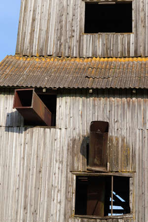 details of an old abandoned building on a farm made of wooden boards, against a background of blue sky, closeup
