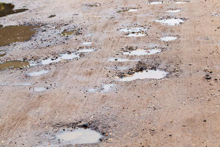 a large number of holes and pits with puddles on the road, closeup