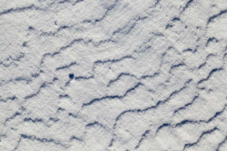 Wavy snowy surface in the winter season, created by wind and frost
