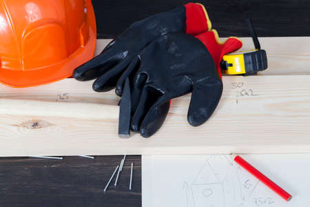 Pencil, pine board, gloves and a construction orange helmet, and a birdhouse drawing that will build
