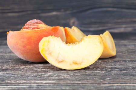 cut ripe peach with traces inside rot and decay, close-up of fruit on cutting board